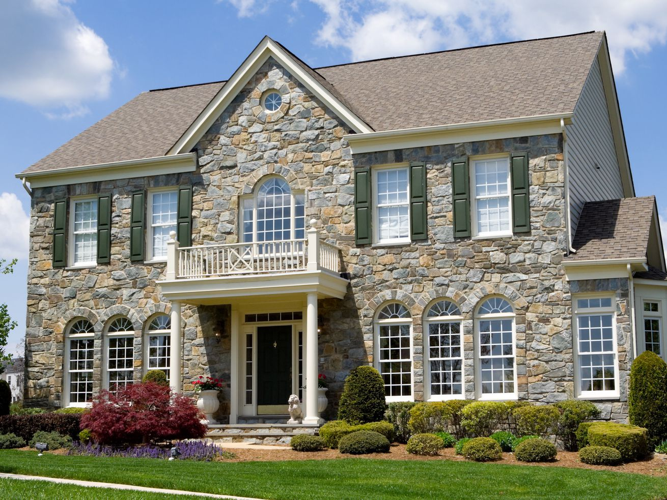 Well landscaped stone single family house.