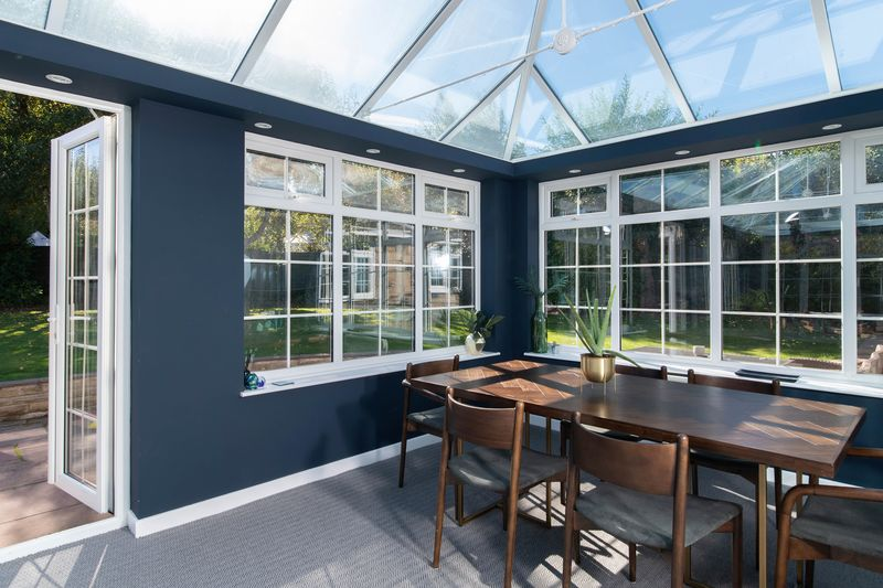 Dining room sunroom with dark blue painted walls.