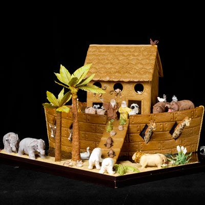 Amazing gingerbread house in the shape of a boat, then elephants, giraffes, and more animals made of marzipan on the boat in pairs.