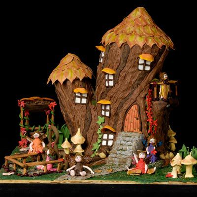 This elaborate amazing gingerbread treehouse set on a creative scene with mushrooms, greenery, and children playing in the garden.