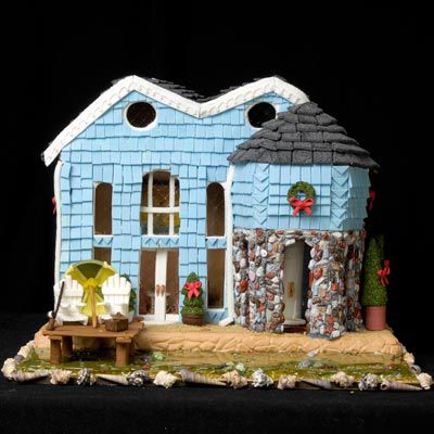 Amazing gingerbread house with light blue icing and decorative green wreath above the door.