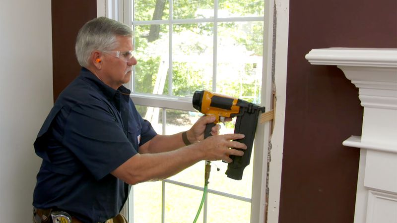 Person using a gap filler to seal drafty windows.